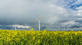 Windmills on a field. And partly cloudy sky in background stock photography
