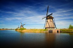 Windmills at riverside on a sunny day, Netherlands Royalty Free Stock Image