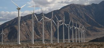 Windmills in a row. Windmills standing in a row on a windy hill giving off power to the surrounding area stock photography