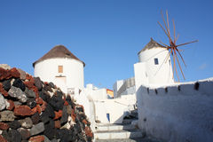 Windmills in Santorini. Picture taken in Oia, white windmills and lava stones Stock Photo