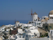 Windmills of Santorini, Greece. Two old windmills among the whitewashed houses in Santorini, Greece Royalty Free Stock Images
