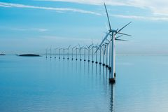 Windmills in the sea with reflection stock photography