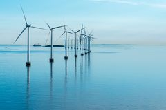 Windmills in the sea with reflection stock images