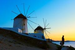 Windmills on the seashore in Mykonos at sundown stock images