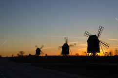 Windmills silhouettes by roadside at sunset Stock Photo