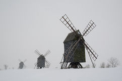 Windmills in snowfall. A raw of old windmills in snowfall, Sweden Royalty Free Stock Photo