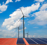 Windmills and solar panels. On orange roof stock photos