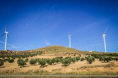 Windmills standing strong using the wind in their favor. On the flat olives lands, where the brownish colors mix with the sky, the wind provides movement for the stock photo