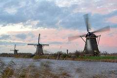 Windmills in sunset. Kinderdijk, the Netherlands. One mill is working - the wings are blurred; grass in the foreground is blurred because of wind Stock Photo