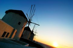 Windmills at Sunset. Windmills stand tall in the deepening sunset at Mykonos, Greece Royalty Free Stock Photos