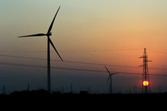 Windmills and Sunset and Electricity poles Stock Images