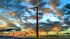 Windmills at sunset. The sun sets as verga falls from the skies over these magnificent uses of wind energy Royalty Free Stock Image