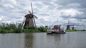 Windmills and tour boat at Kinderdijk Royalty Free Stock Image