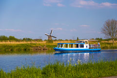 Windmills and touristic boat reflected in canals at Kinderdijk, Holland Stock Photos