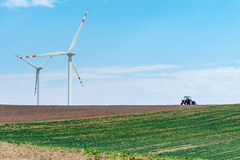 Windmills and tractor on the field Royalty Free Stock Images