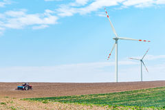 Windmills and tractor on the field Stock Photos