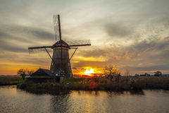Windmills and water canal on sunset in Kinderdijk, Holland Royalty Free Stock Photos
