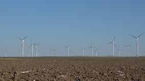 Windmills, wind turbines, agriculture wheat field generator power, electricity stock video footage