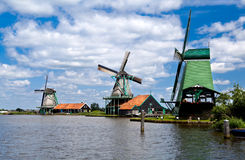 Windmills in Zaanse Schans. Three windmills in Zaanse Schans close to river over beautiful sky royalty free stock photo