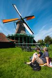 Windmills in Zaanse Schans, Netherlands. Famous Windmills by the river in Zaanse Schans, Netherlands. Some people are admiring it on the grass stock image