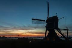Windmolen in Holland bij zonsondergang met lage mist over het platteland royalty-vrije stock fotografie