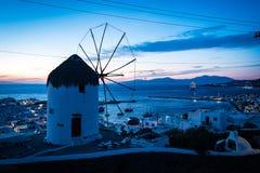 Windmolen op Mykonos die de stad en de haven overzien bij schemer Stock Foto