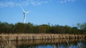 Windmolen voor stroomproductie dichtbij vijver stock videobeelden