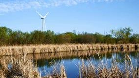 Windmolen voor stroomproductie dichtbij vijver bij schemer stock videobeelden