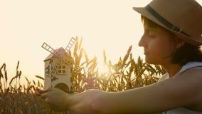 Windmolens in de hand van een jong meisje op een achtergrond van gouden oren van tarwe Een vrouw bekijkt de roterende bladen van  stock video