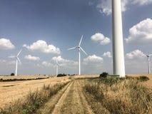 Windmolens in een geoogste die tarwe in de recente zomer wordt ingediend royalty-vrije stock fotografie