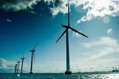 Windmolens in een rij tegen zon Stock Foto's