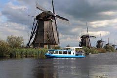 Windmolens en tourboat in Kinderijk, Holland Stock Foto's