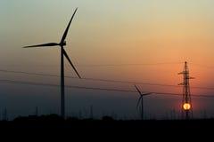 Windmolens en Zonsondergang en Elektriciteitspolen Stock Afbeeldingen