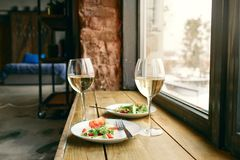 Windo di legno di vetro del vino bianco dell'insalata di verdure sana di due piatti Fotografie Stock Libere da Diritti