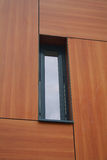 Window. Close up of a window surrounded by timber effect cladding panels on a modern building Royalty Free Stock Photography