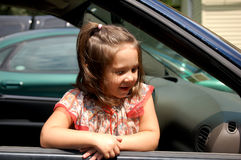 In the window. Four year old girl leaning out of the window of a car Stock Photos