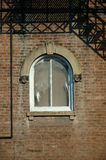 Window. On a 1920s brick building, framed by the fire escape stairway and pipes stock images