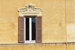 Window. Old shuttered window with decorative relief rome italy creates a typical mediterranean scene Stock Photo
