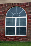 Window. Large window in red brick house with curved arch at top, many panes of glass Stock Images