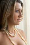 By the window. Romantic women in pearls waiting by the window royalty free stock photo