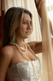 By the window. Romantic women in pearls waiting by the window royalty free stock photography