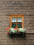 Window. Ancient wooden window with flowers surrounded by timber shingles Stock Photography