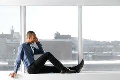 At the Window. Business man sitting on a window frame Stock Photography