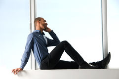 At the Window. Business man sitting on a window frame Stock Images