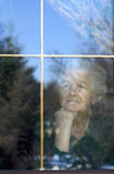 Through the window. Elderly woman looking through the window Royalty Free Stock Image
