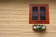 Window. An old window and flowers in a wooden wall Stock Images