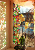 Window. Painting on a window, drawn the paints of stained-glass windows. With an orchid on a window-sill Stock Photos