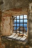 Window on abandoned ruins with rusty bars overlooking Adriatic sea. Square window on abandoned ruins with rusty window bars overlooking Adriatic sea and nearby royalty free stock photo