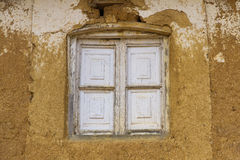 Window in Adobe House. Old wooden window and closed . Exterior house of adobe or mud and straw. Paint on window and wall Royalty Free Stock Photo