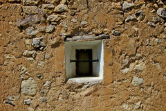 Window on adobe. A window in the middle of an adobe and stones wall, with a curious metal bar to avoid burglars Royalty Free Stock Photography